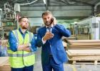 мъже в дърводелски цех обсъждат инвестиция