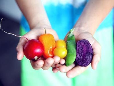 жена държи в ръцете си плодове и зеленчуци